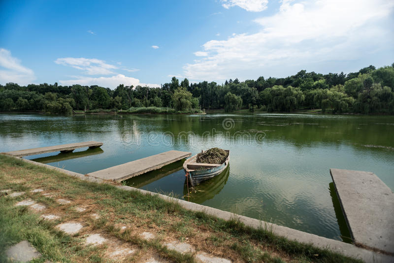 Old Wooden Row Boat. Old wooden boat on green lake with forrest trees and blue sky with clouds royalty free stock photography