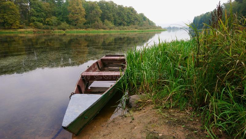 Old wooden rowing boat on the river royalty free stock image