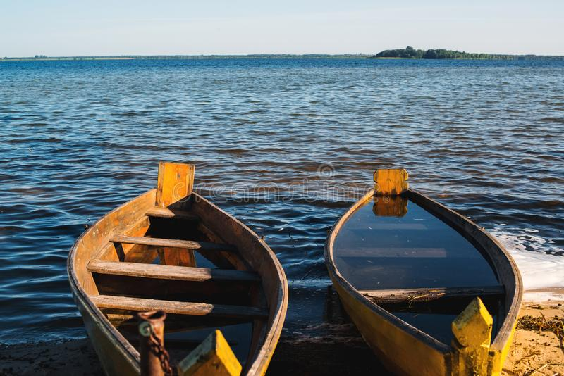 Old wooden rowing boats on a lake. Two fishing boats at beautiful sunset in summer morning. Summer vacation. Beautiful lake with stock images