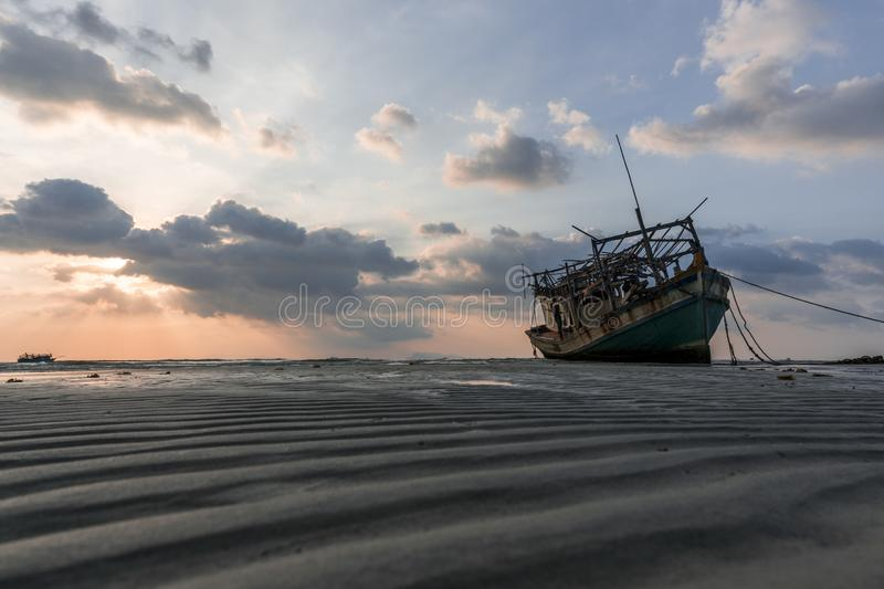 The old wooden ruined fishing boat set aground on the beach at Sunset time stock images