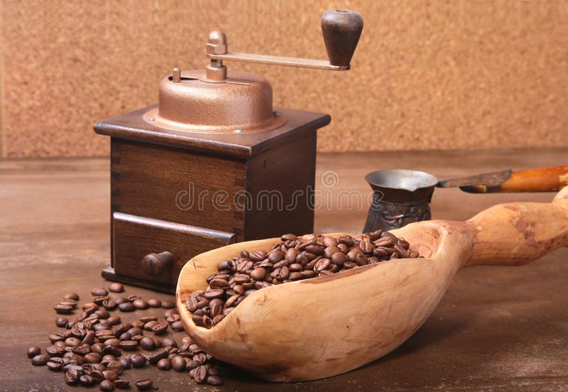 Old wooden scoop with coffee beans, coffee grinder and Cezve on dark stone table. stock photography
