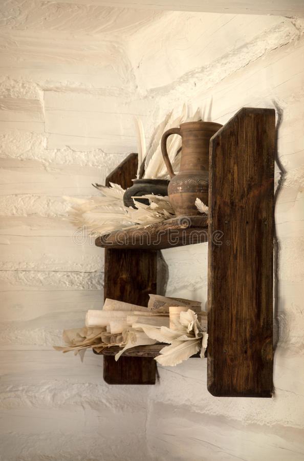 Old wooden shelf with jug, paper and pens stock photography