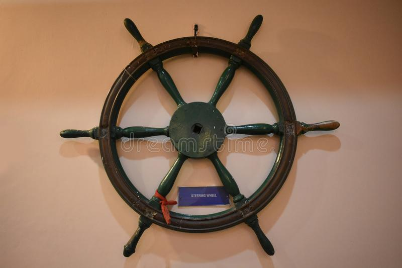 Old wooden ship steering wheel rudder on a wall. Vintage wooden ship steering wheel rudder on a half light wall. It uses on boat or ship to direction the path on stock image