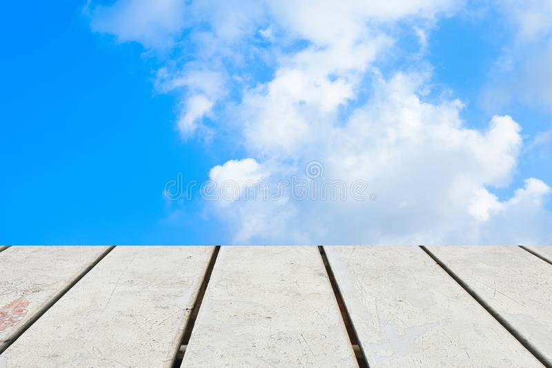 Old Wooden table with blue sky white cloud background royalty free stock photo