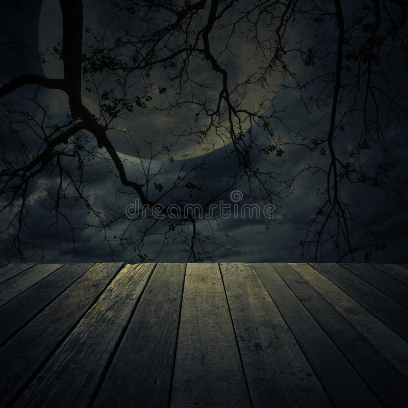 Old wooden table over dead tree, Halloween background royalty free stock photos