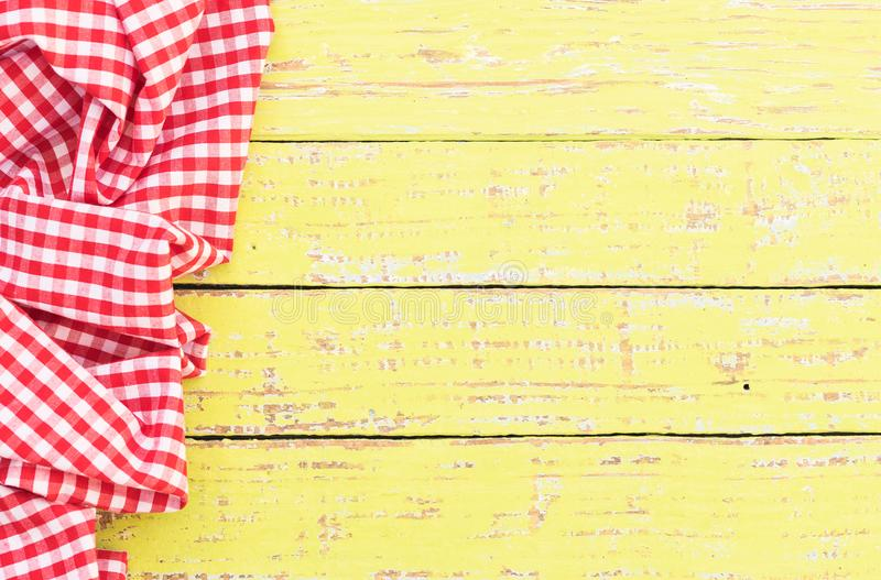 Old wooden table with red checked tablecloth on left side. Yellow wooden table background rustic texture, with red checkered tablecloth, high angel view royalty free stock photos