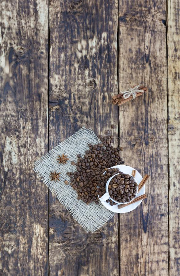 Grain coffee in a cup, which stands on a sackcloth from burlap. Cinnamon on a platter and tied with a rope. Anise stars complement stock photo