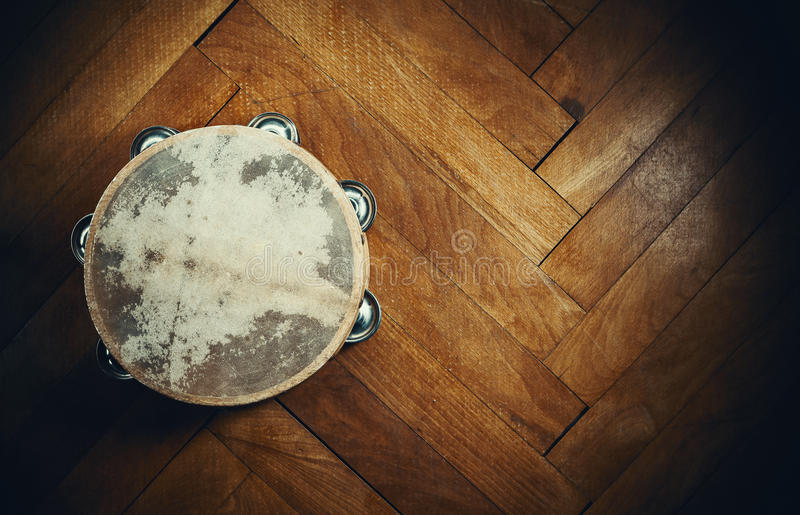 Old Wooden Tambourine. On brown parquet stock image