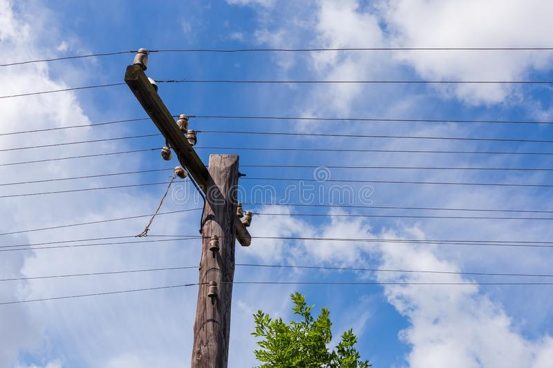 Old wooden telegraph pole with spar, insulators and open wires. Upper part of the old wooden telegraph pole with utility spar, insulators and open telephone royalty free stock photo