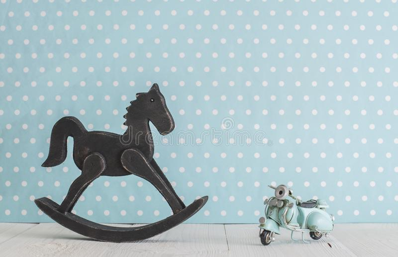 Old wooden toy horse rocking chair and blue vintage motorcycle stock photo