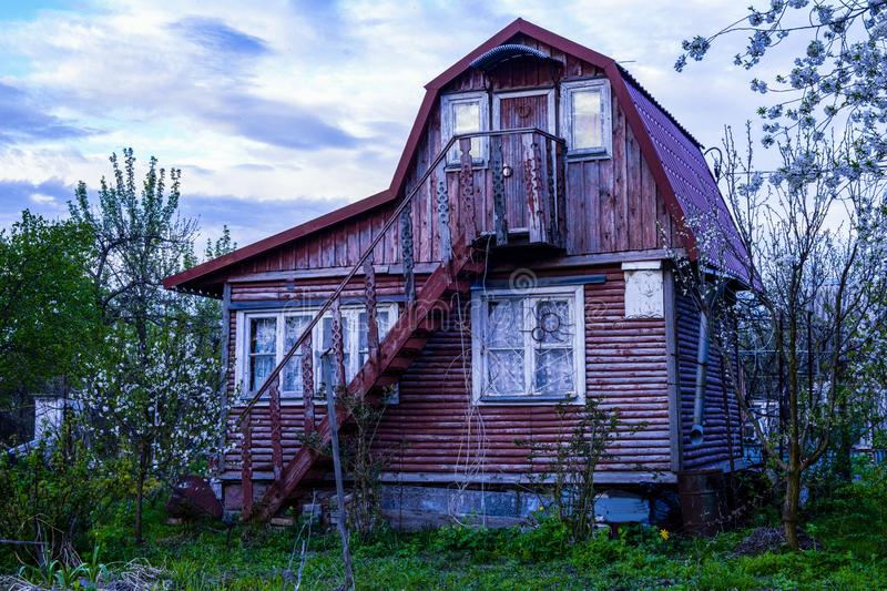 Old wooden two-storey abandoned burgundy-colored country house royalty free stock images