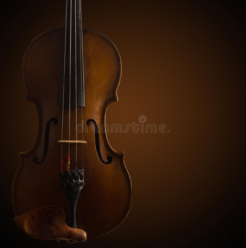 Old wooden violin on dark brown. Background stock images