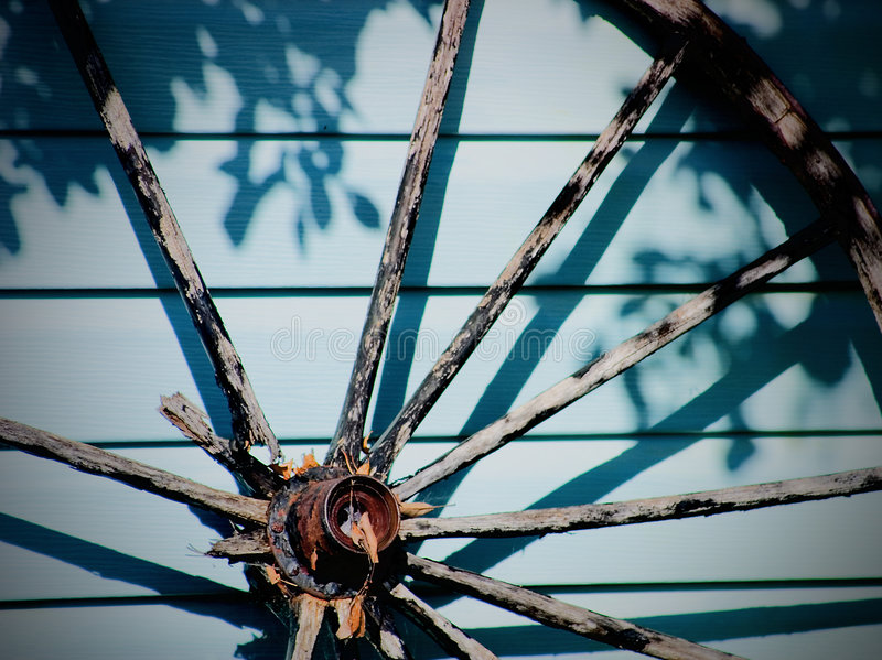 Old wooden wagon wheel. Leaning against the outside of a blue building stock images