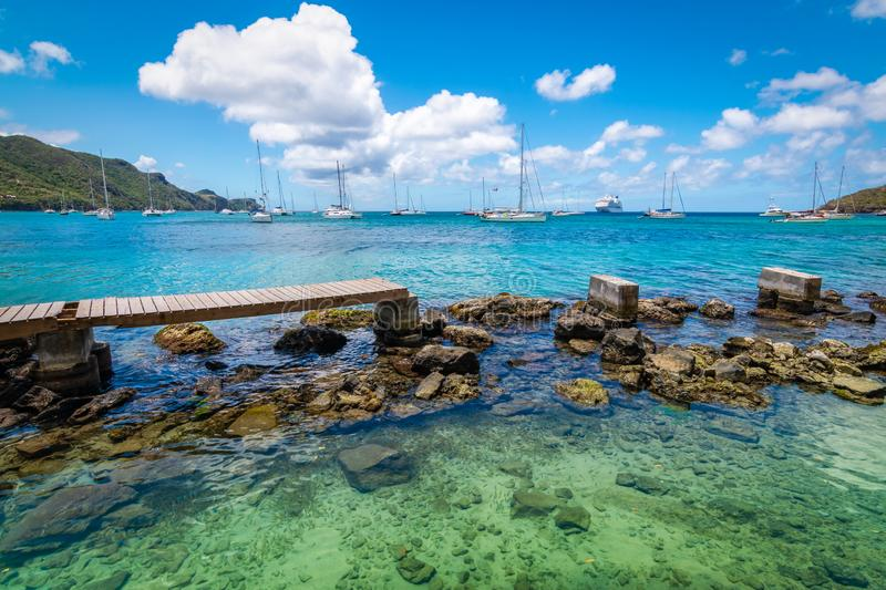 Old wooden walkway over the water to the beach in Bequia. royalty free stock photos