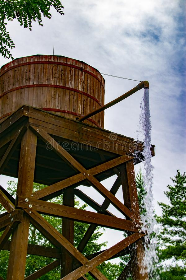 An old wooden water tank from which water comes out.  royalty free stock photo