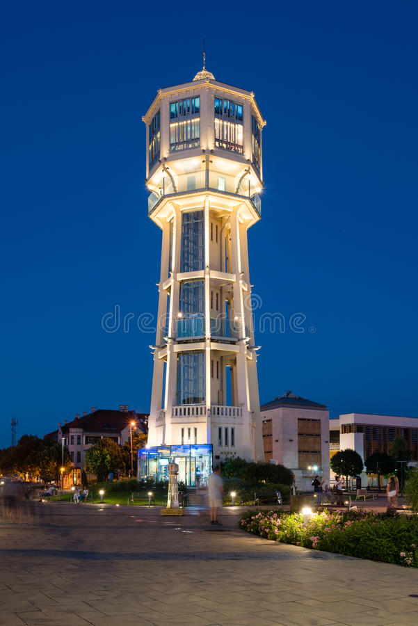 Old wooden water tower in Siofok, Hungary. SIOFOK, HUNGARY - AUGUST 24, 2016: Old wooden water tower on main square of city Siofok with night illumination royalty free stock photography