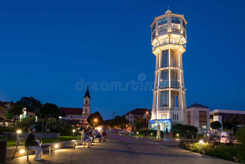 Old wooden water tower in Siofok, Hungary. SIOFOK, HUNGARY - AUGUST 24, 2016: Old wooden water tower on main square of city Siofok with night illumination royalty free stock photos