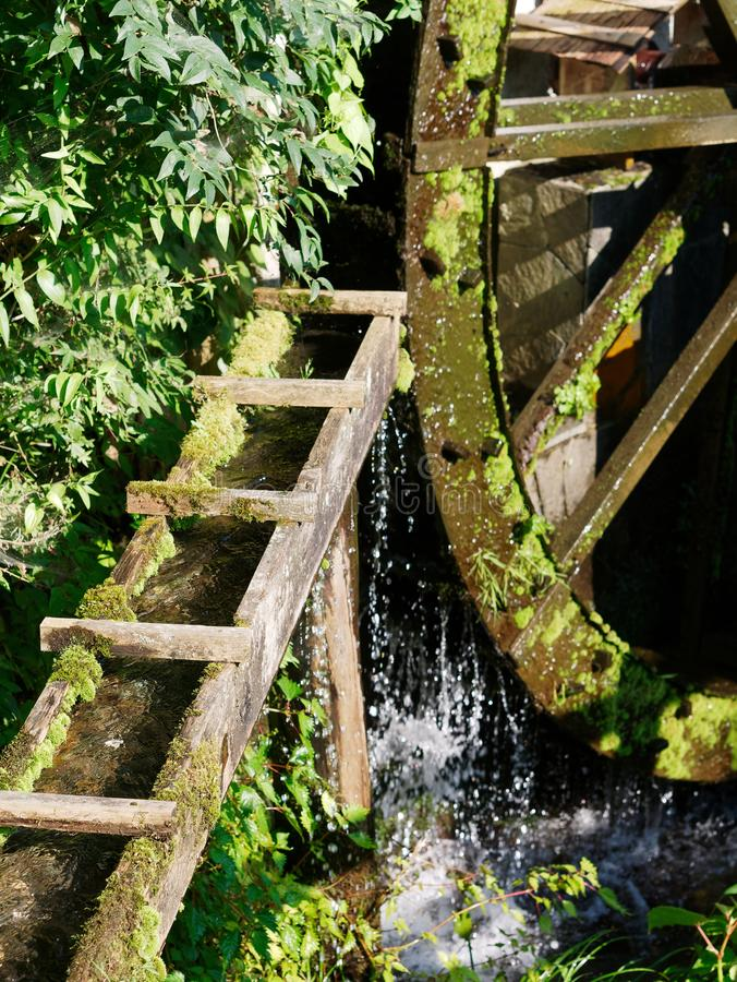 Old wooden waterwheel covered with moss. Flowing water to the mill. royalty free stock photos