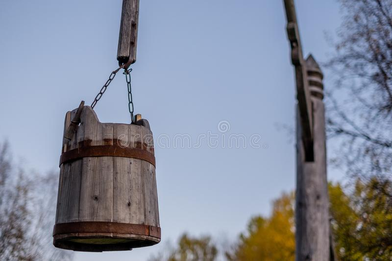 Old wooden well with a bucket on the pole stock image
