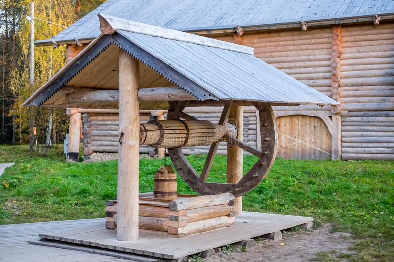 Old wooden well with a bucket on the pole royalty free stock photos