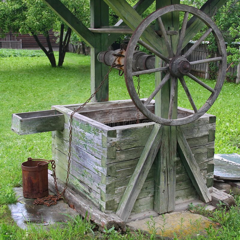 Old wooden well. Old traditional well with a rusty pail stock photo