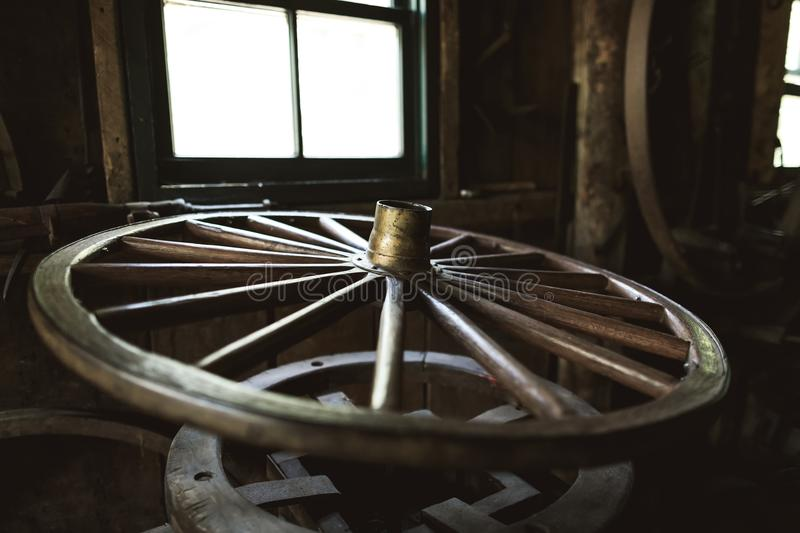 Old wooden wheel of the horse cart in the ancient forge. The old car wheel is considered to be the symbol of happiness and luck talisman in the cultures of stock images