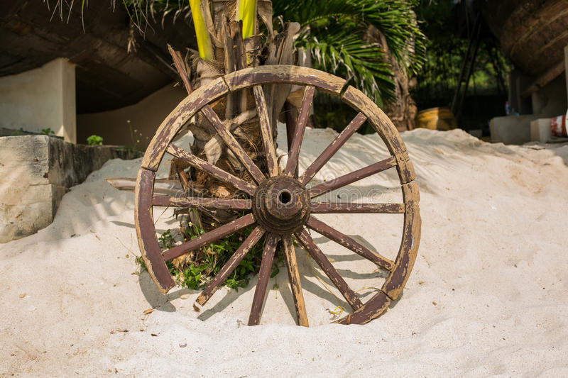 Old wooden wheel on sand. Old brown wooden wheel on sand beach royalty free stock photos