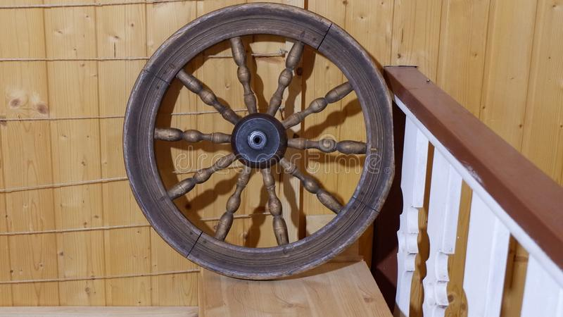 Old wooden wheel on the wall of the house natural wooden texture. stock image