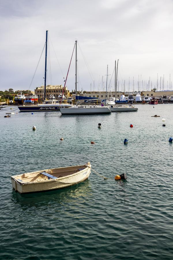 An old wooden white boat at Manoel Island Yacht Yard in Gzira, Malta, various types of boats in the background. MANOEL ISLAND, GZIRA, MALTA - MARCH 06, 2018: An stock images