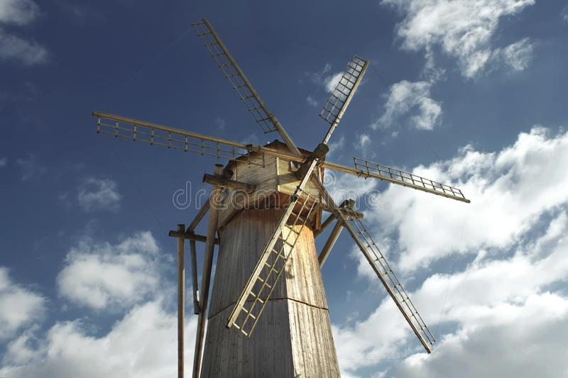 Old wooden windmill against a blue sky in sunny day close-up stock photos