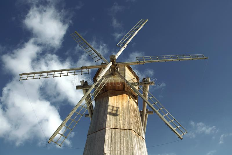 Old wooden windmill against a blue sky in sunny day close-up.  stock images