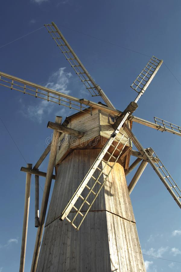 Old wooden windmill against a blue sky in sunny day close-up.  royalty free stock photo