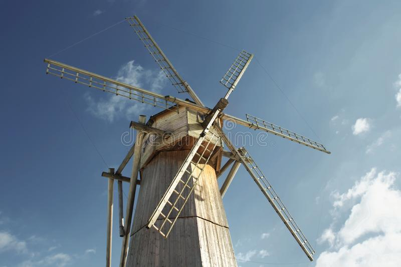 Old wooden windmill against a blue sky in sunny day close-up.  stock photography