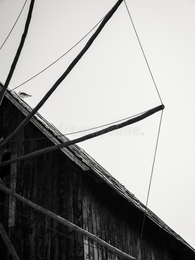 Old wooden windmill in the background of the blue sky stock photos