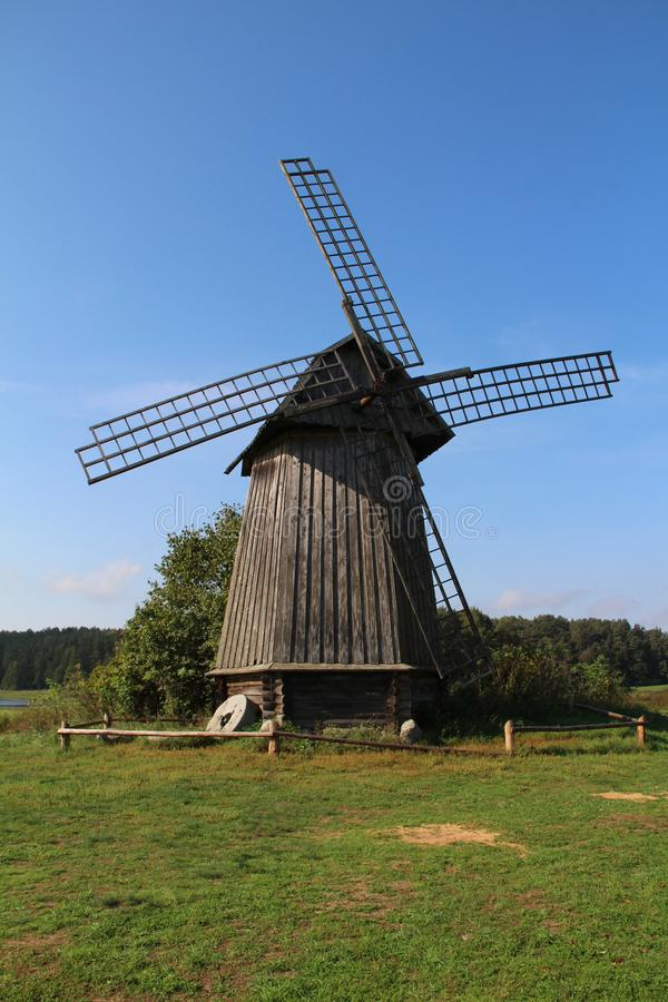 Old wooden windmill one. Old wooden windmill on a green field in nature royalty free stock photography
