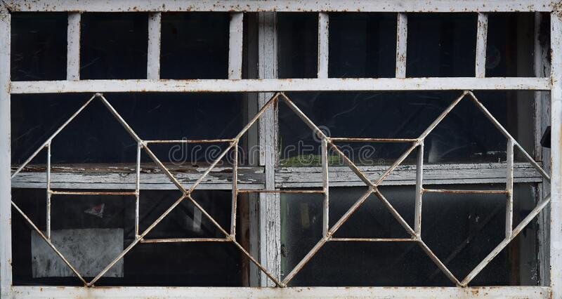 Old wooden window behind a metal grate. Vintage texture.  stock photography