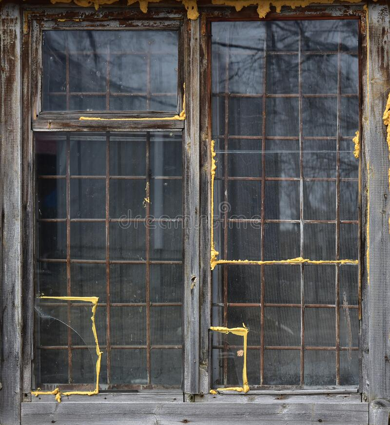 Old wooden window behind a metal grate. Vintage texture.  stock photos