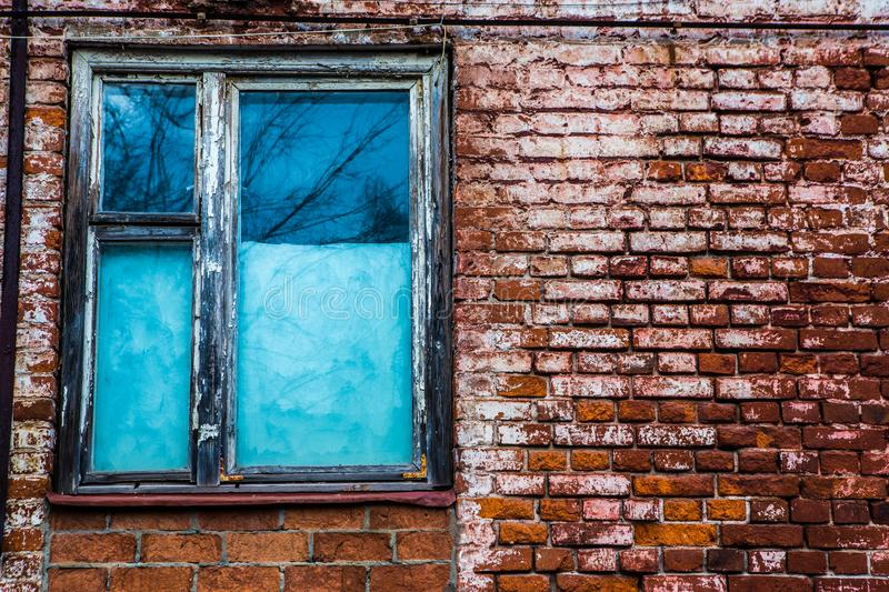 Old wooden window in an old brick wall. Old wooden window. Old brick wall. Grunge background royalty free stock image