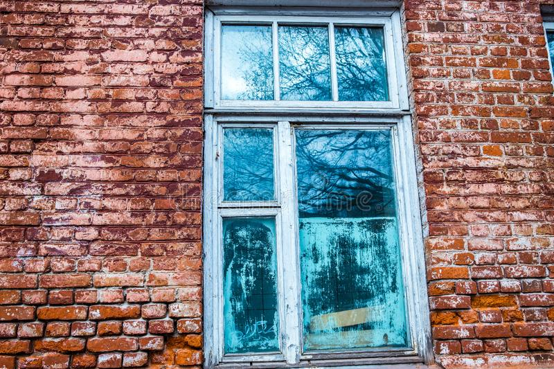 Old wooden window in an old brick wall. Old wooden window. Old brick wall. Grunge background stock photo