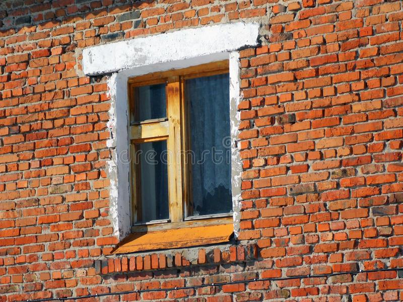 An old wooden window. On the weathered red brick wall royalty free stock photo