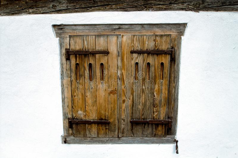 Old wooden window in a white wall. Building of Switzerland. stock photo
