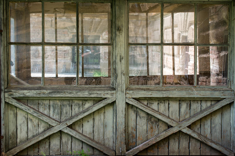 Old wooden windowed wall. Old, gray, cracked wooden windowed door - texture, background royalty free stock photos