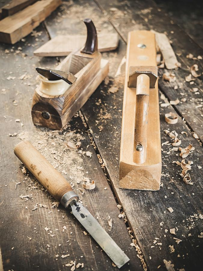 Old woodworking hand tool: wooden plane, chisel and in a carpentry workshop on dirty rustic table covered with sawdust. Background side view royalty free stock photography