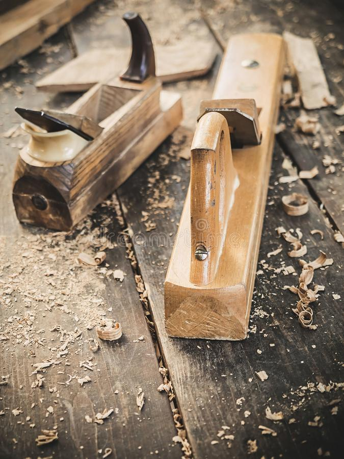 Old woodworking hand tool: wooden plane, chisel and in a carpentry workshop on dirty rustic table covered with sawdust. Background side view royalty free stock image