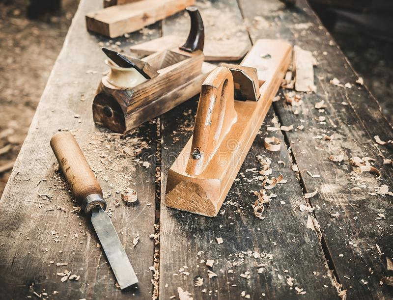 Old woodworking hand tool: wooden plane, chisel and drawing knife in a carpentry workshop on dirty rustic table covered. With sawdust background side view royalty free stock image