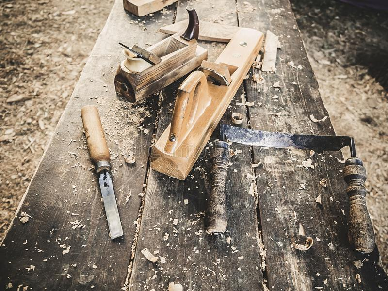 Old woodworking hand tool: wooden plane, chisel and drawing knife in a carpentry workshop on dirty rustic table covered. With sawdust background side view royalty free stock images