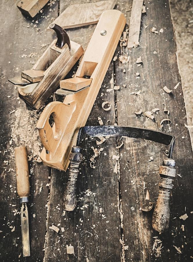 Old woodworking hand tool: wooden plane, chisel and drawing knife in a carpentry workshop on dirty rustic table covered. With sawdust background top view royalty free stock image