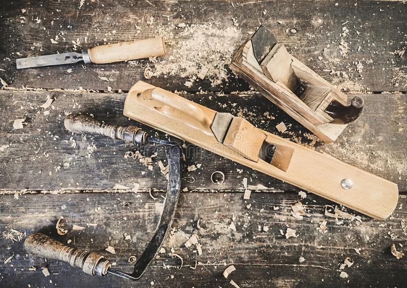 Old woodworking hand tool: wooden plane, chisel and drawing knife in a carpentry workshop on dirty rustic table covered. With sawdust background top view stock image