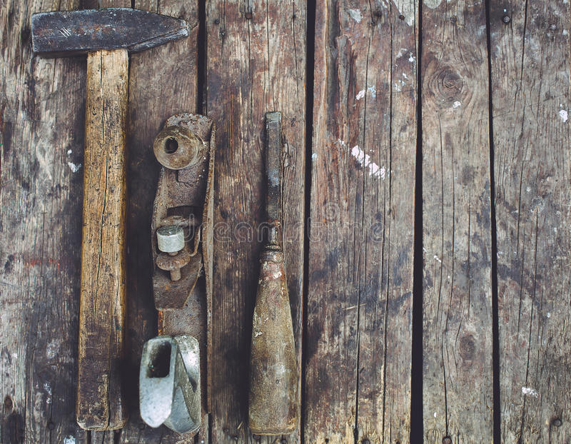 Old woodworking tools lie on a wooden surface. Hammer, planer, chisel royalty free stock photography