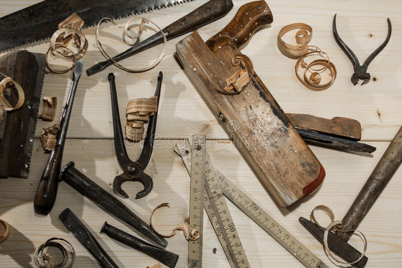 old woodworks tools: wooden planer, hammer, chisel in a carpentry workshop on wood background stock photo